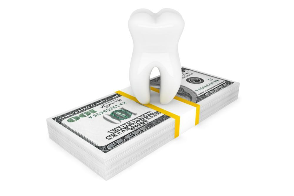 a tooth atop a stack of bills | dental cleanings highpoint nc