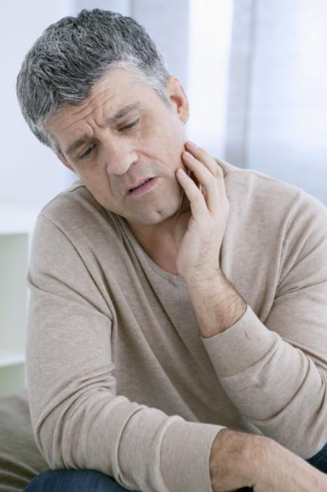 a man holds his hand to his cheek | root canals highpoint nc