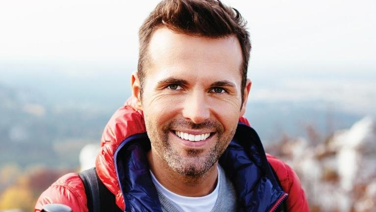 Man smiling and wearing red jacket