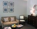 the waiting area of our high point, nc dental office, featuring a couch, table, chair, and wall art